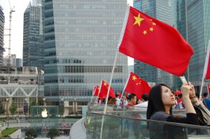 A young woman uses her iPhone to take a photo in Luijiazui, China with an Apple store visible in the background. China has become a vital market for Apple products.