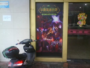 A poster for World of Warcraft outside an internet cafe in Shanghai. The low cost cafes allow access to the internet for Chinese citizens without computers and give gamers a place to play.