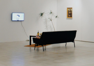 "The original exhibition of ""When you think about painting do you think about something like this"" features a living room setup within the exhibit space."